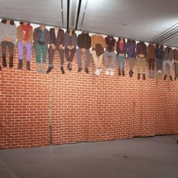 People Sitting on Top of a Red Brick Wall . 2014